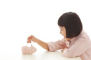 貯金箱にお金を入れるおかっぱの女の子の写真素材 [FYI02685715]