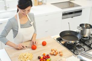 明るいキッチンで野菜を切る女性の写真素材 [FYI02685726]