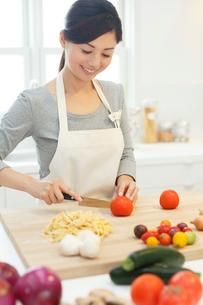 明るいキッチンで野菜を切る女性の写真素材 [FYI02685764]