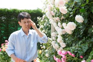 頭痛に顔をしかめる中年男性の写真素材 [FYI02685782]