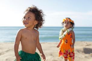 海岸でフラダンスの衣装を着ているハーフの女の子と男の子の写真素材 [FYI02685798]