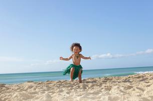 腰みのをつけて海岸を走るハーフの男の子の写真素材 [FYI02685917]