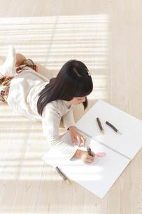 スケッチブックに色鉛筆で絵を描く女の子の写真素材 [FYI02685957]