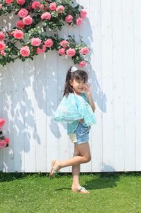 バラの咲く庭でポーズをとる女の子の写真素材 [FYI02686027]