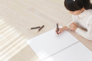 スケッチブックに色鉛筆で絵を描く女の子の写真素材 [FYI02686072]