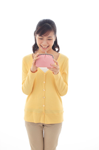財布を持ちポーズをとる女性の写真素材 [FYI02686101]