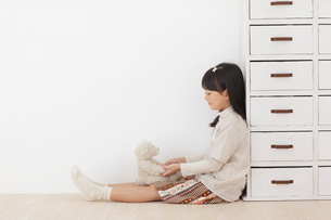 くまのぬいぐるみとフローリングの床に座る女の子の写真素材 [FYI02686185]