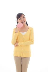 財布を持ちポーズをとる女性の写真素材 [FYI02686188]