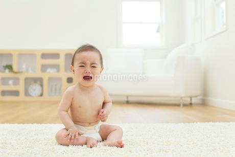 リビングで泣く裸の赤ちゃんの写真素材 [FYI02686412]