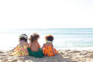 フラダンスの衣装を着て海岸に座っているハーフの子ども達の写真素材 [FYI02686424]