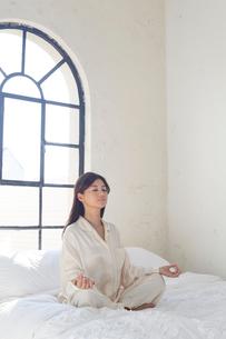 大きな窓のある広い寝室でヨガをする女性の写真素材 [FYI02686447]