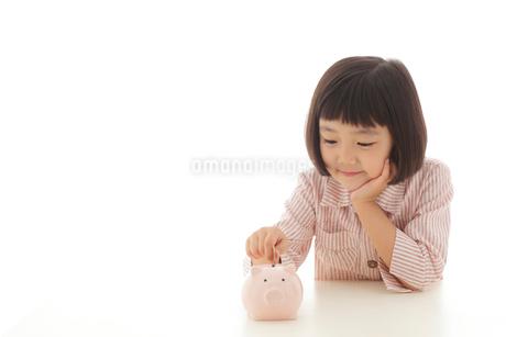 貯金箱にお金を入れるおかっぱの女の子の写真素材 [FYI02686459]