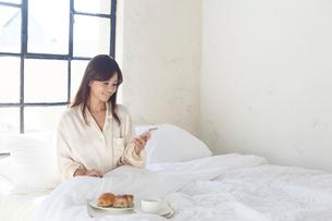 広いベッドルームで携帯を見ながら朝食を食べる女性の写真素材 [FYI02686467]