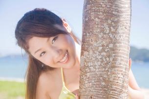 アカタコノキから顔を覗かせる水着女性の写真素材 [FYI02686512]