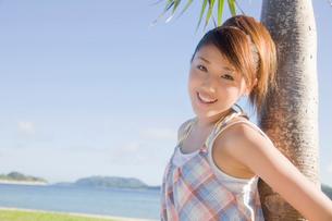 アカタコノキに寄りかかり微笑む女性の写真素材 [FYI02686527]
