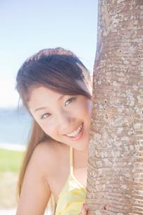 アカタコノキから顔を覗かせる水着女性の写真素材 [FYI02686539]