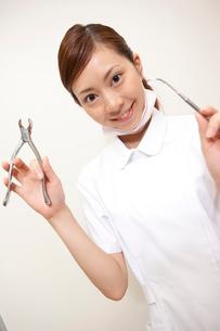 口腔鏡とペンチを持って微笑む歯科衛生士の写真素材 [FYI02686543]