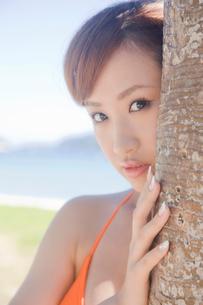アカタコノキから顔を覗かせる水着女性の写真素材 [FYI02686565]
