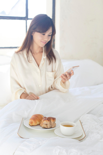 広いベッドルームで携帯を見ながら朝食を食べる女性の写真素材 [FYI02686693]