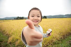 田園でおにぎりを食べる女の子と母親の写真素材 [FYI02686699]