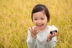 田園でおにぎりを食べる女の子の写真素材 [FYI02686782]