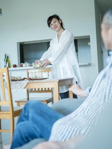 食事の準備をする女性とソファでくつろぐ男性の写真素材 [FYI02686825]