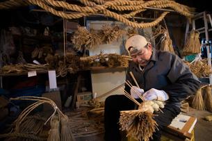 冬の農閑期にしめ縄作りする80代男性の写真素材 [FYI02686881]