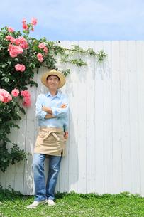 バラと白い板壁の前に立つ中年男性の写真素材 [FYI02687037]
