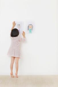 お父さんとお母さんの絵を壁に貼るおかっぱの女の子の写真素材 [FYI02687062]