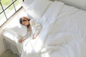 大きな窓のある広い寝室で眠る女性の写真素材 [FYI02687108]