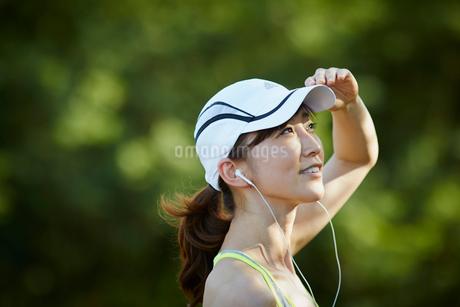 イヤホンをつけランニングキャップを被った女性の横顔の写真素材 [FYI02687316]