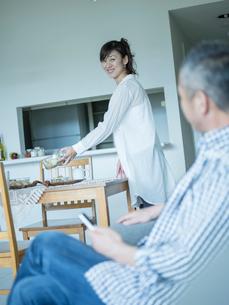 食事の準備をする女性とスマートフォンを持つ男性の写真素材 [FYI02687343]