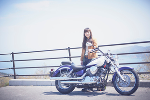バイクの横に立つ女性の写真素材 [FYI02687520]