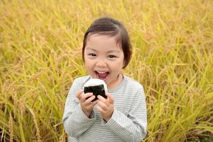 田園でおにぎりを食べる女の子の写真素材 [FYI02687588]