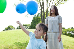 風船を持つ女の子と母親の写真素材 [FYI02687657]