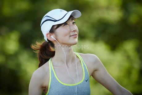 イヤホンをつけランニングキャップを被った女性の写真素材 [FYI02687725]