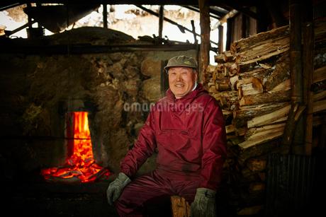 炭焼き窯の前に座る笑顔のシニア男性の写真素材 [FYI02688855]
