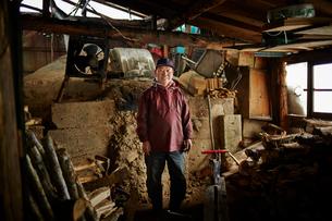 作業着姿の炭焼き小屋の笑顔のシニア男性の写真素材 [FYI02688865]