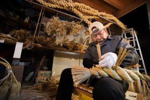 冬の農閑期にしめ縄作りする80代男性の写真素材 [FYI02688922]