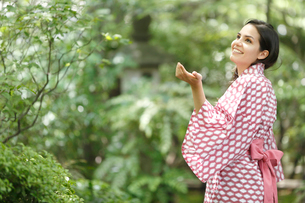 緑の木々を眺める浴衣姿の外国人女性の写真素材 [FYI02689057]