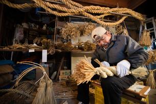 冬の農閑期にしめ縄作りする80代男性の写真素材 [FYI02689065]