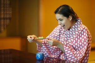 和菓子を見て喜ぶ浴衣姿の外国人女性の写真素材 [FYI02689103]