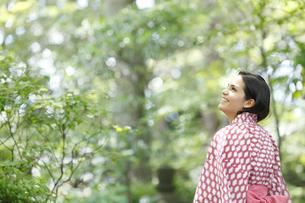緑の木々を眺める浴衣姿の外国人女性の写真素材 [FYI02689155]