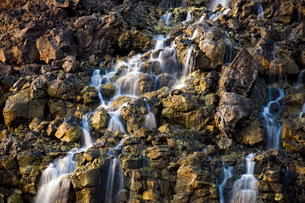 Brine falls from volcanic rock drop off to a runoff stream.の写真素材 [FYI02689620]