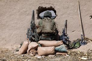 A U.S. Marine sniper observes his sector at a patrol base neの写真素材 [FYI02689673]