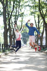 ジャンプする外国人カップルの写真素材 [FYI02689701]