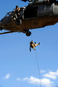 A pararescueman rappels from an HH-60 Pavehawk helicopter.の写真素材 [FYI02690385]