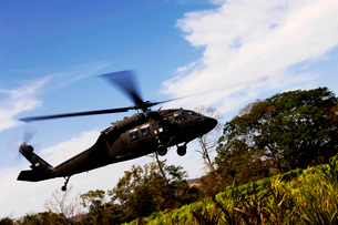 A U.S. Army UH-60 Black Hawk helicopter flies out of an emerの写真素材 [FYI02690421]