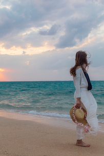 波打ち際で麦わら帽子を持つ女性の写真素材 [FYI02690429]