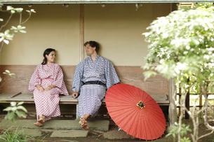 浴衣姿でくつろぐ外国人カップルと和傘の写真素材 [FYI02690499]